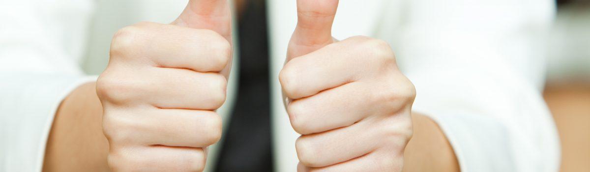 Vrouw met duimen omhoog voor de 10 voordelen van stoppen met roken
