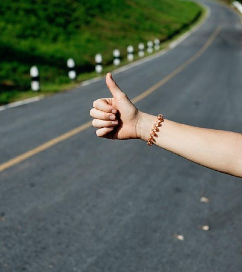 Iemand steekt zijn duim omhoog langs de weg